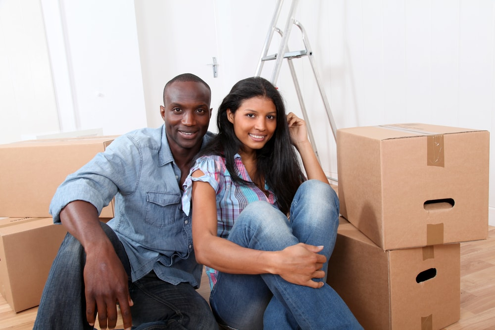 Cheerful couple sitting in empty apartment with moving boxes
