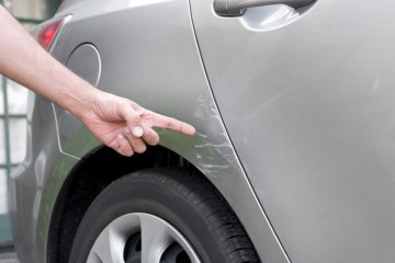 Close-up of hand pointing to scrape mark on gray car.