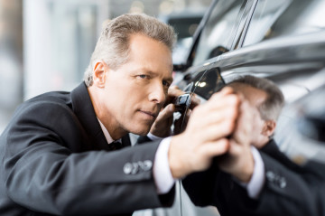 Perfect lines.  Mature grey hair businessman examining car at the dealership