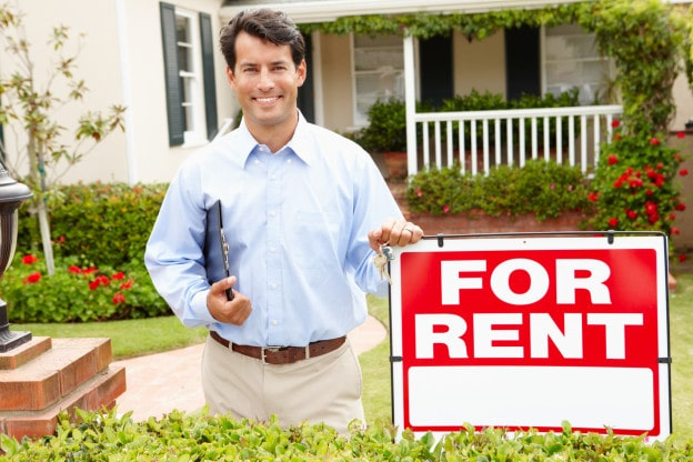 Real estate agent at work holding clipboard smiling to camera