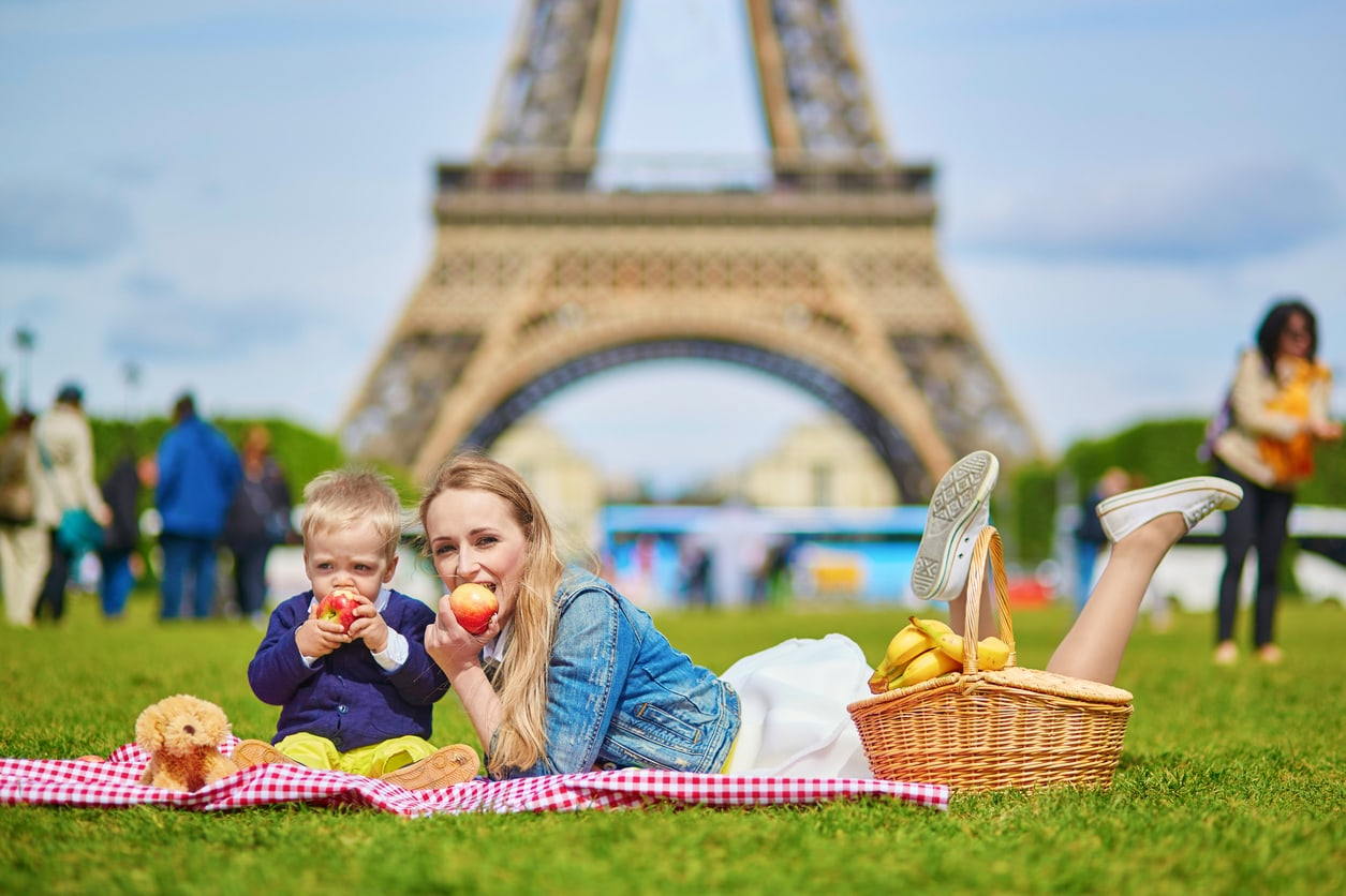Happy family of two, mother and little toddler boy, having picnic in Paris near the Eiffel tower and eating apples