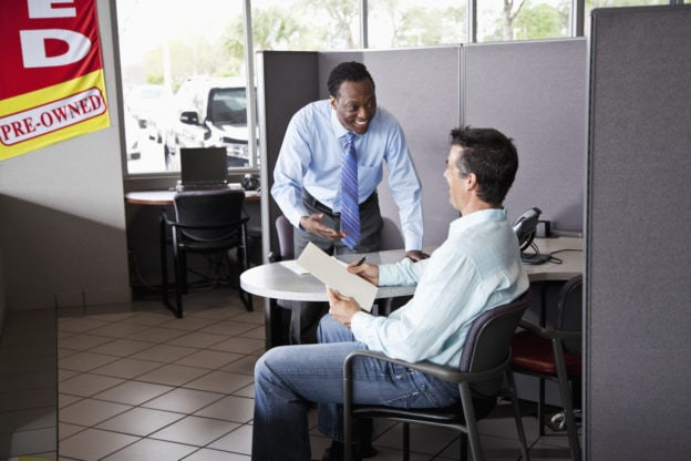 Car salesman with customer signing paperwork to buy used car