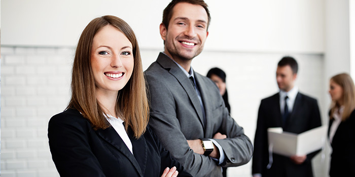 Front view of smiling business executives with three more people doing buisness in the background