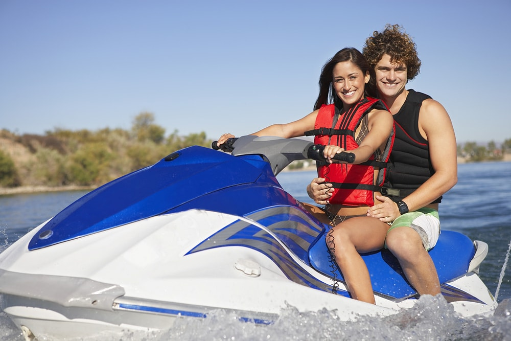 Portrait of a happy couple riding jet ski on lake