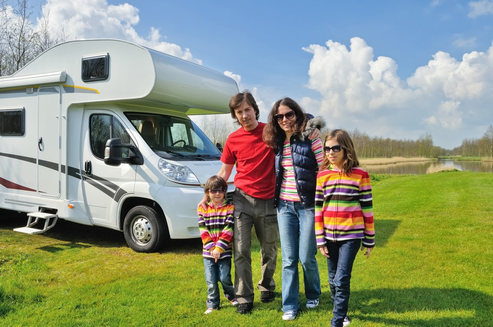 Happy family on vacation standing in front of motorhome