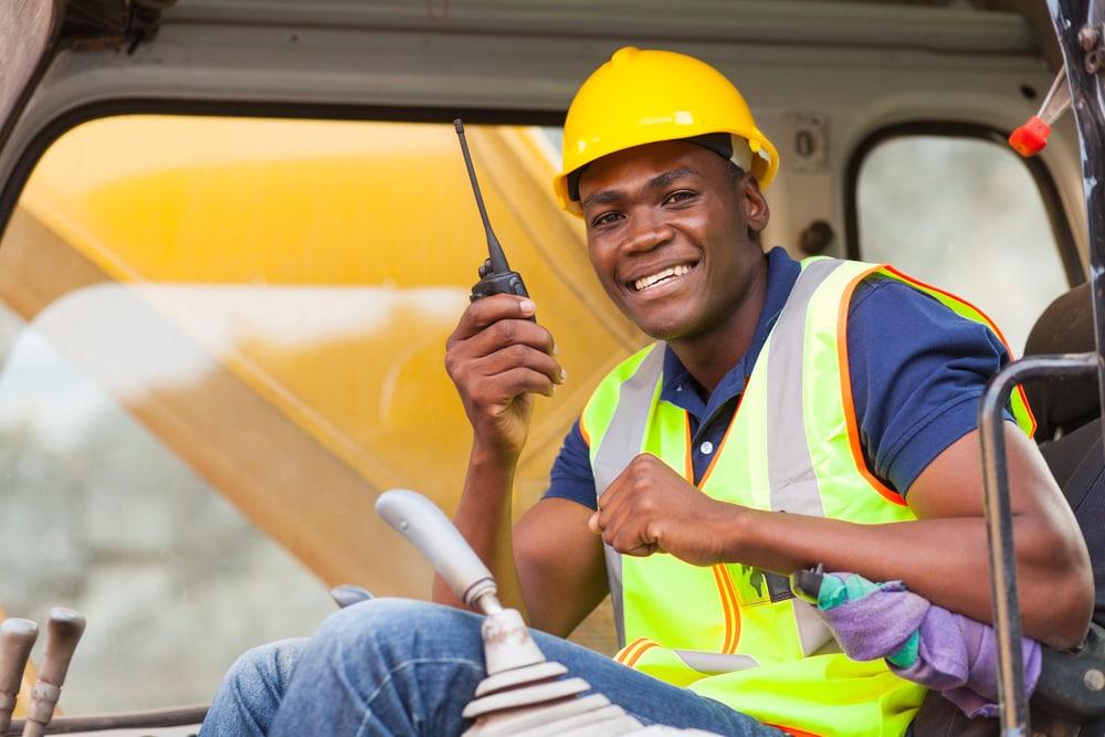 bulldozer operator talking on walkie talkie at construction site