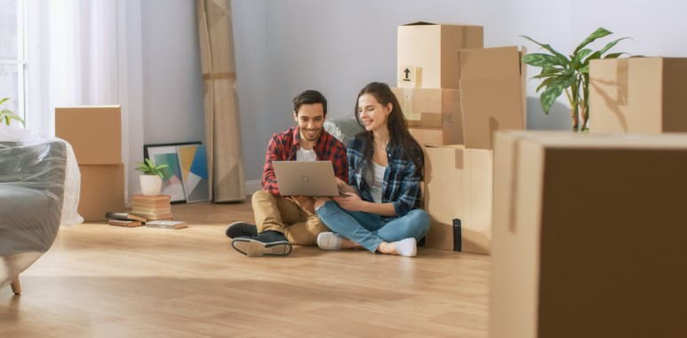 couple sitting in new apartment looking at renters insurance quotes at laptop