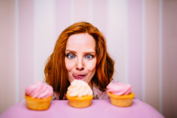 Young red head woman really wants to eat pink cupcakes