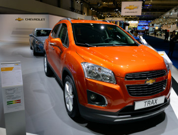 Chevrolet Trax compact SUV on display at the 2014 Brussels motor show. People in the background are looking at the cars.
