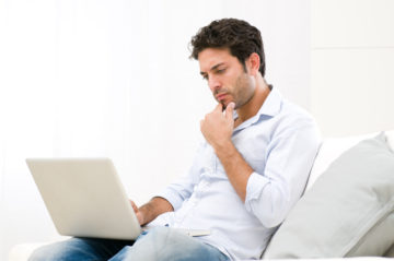 Young man looking at his laptop computer with pensive expression
