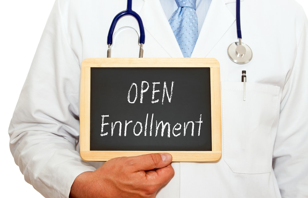 "Doctor holding chalkboard that reads ""Open Enrollment"" on white background"