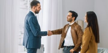 young couple shaking hands with landlord renting a home