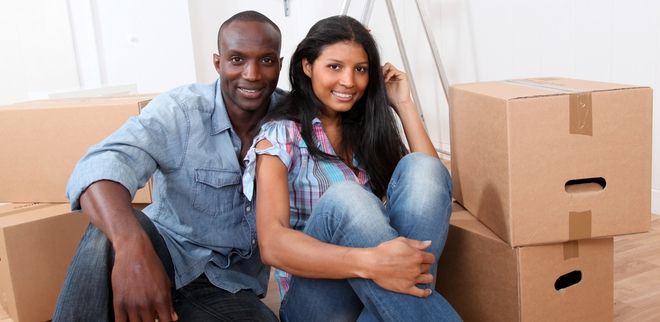 Happy couple in their rented home with moving boxes