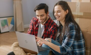 young couple in their apartment looking for renters insurance at laptop