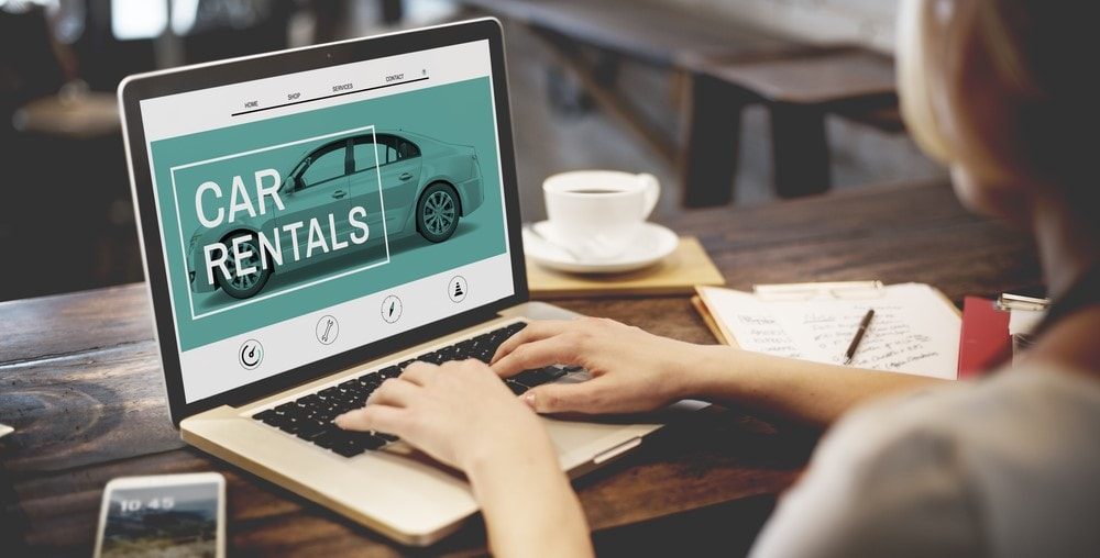 woman looking at rental car in laptop screen that says car rentals
