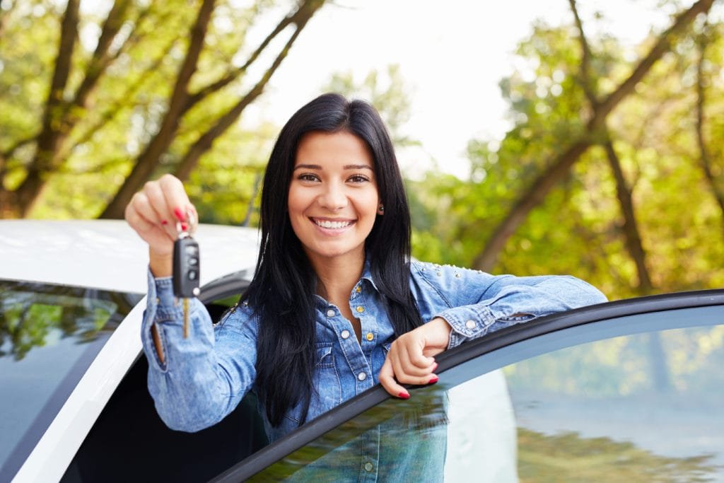 happy girl holding car keys standing with car door non owners insurance
