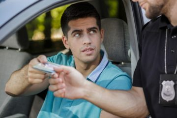 man giving his drivers license to a cop that pulled him over drivers license points