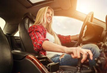 young woman changing gears while driving manual vs. automatic transmission