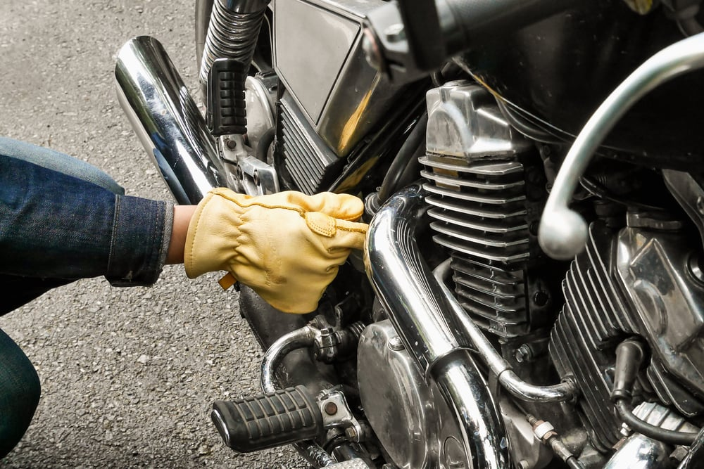 man with glove checking motorcycle for maintance checklist