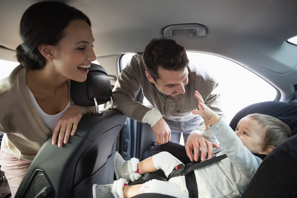 parents getting their baby into a car seat with requirements