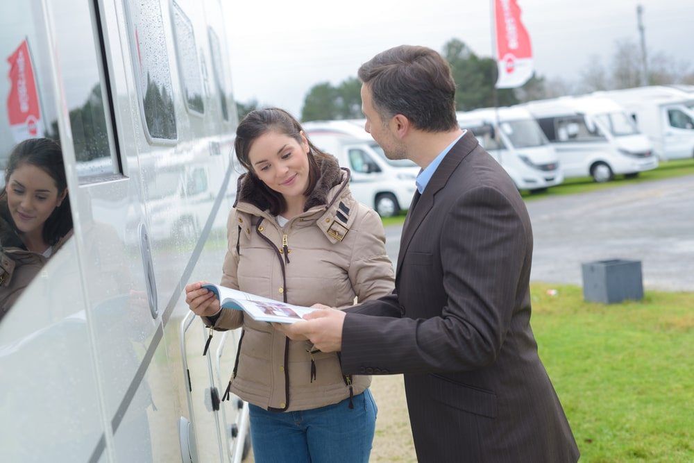woman looking at a used camper with salesman