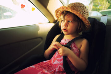 little girl with a hat sitting inside a car on car seat