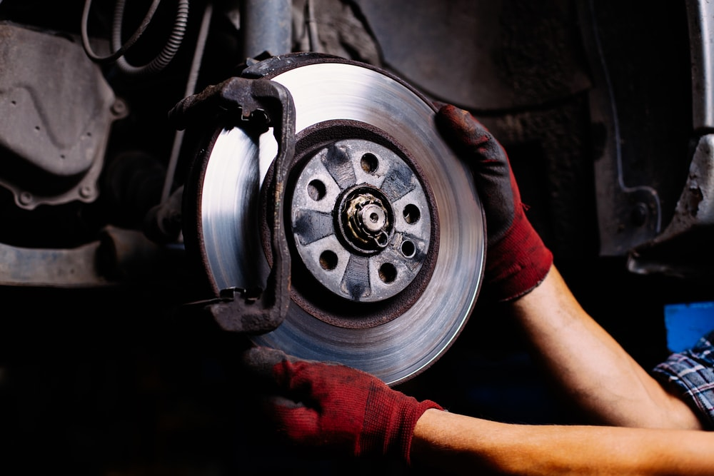 mechanic installing anti lock brakes on a car with hands