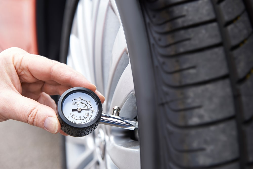 hand with tire pressure gauge on a car wheel