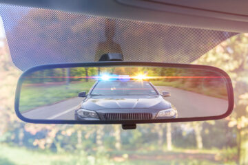 rearview mirror with a police car pulling the driver over
