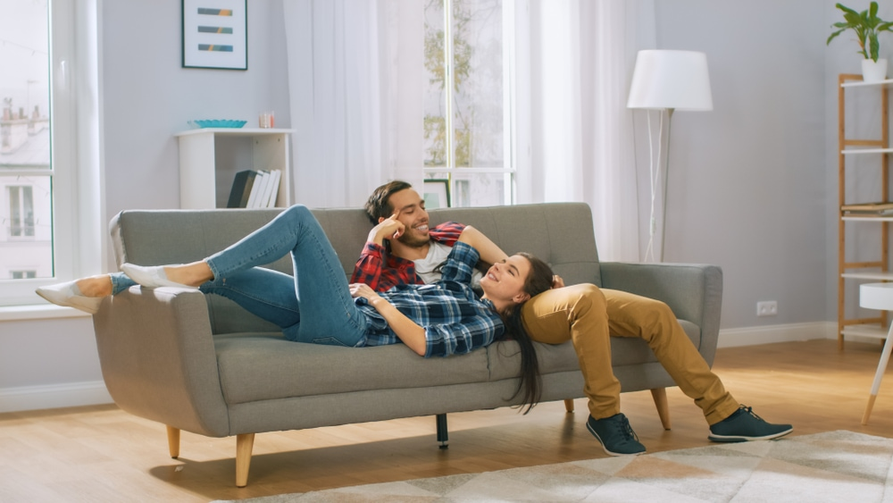 happy couple on the couch of their first rented apartment