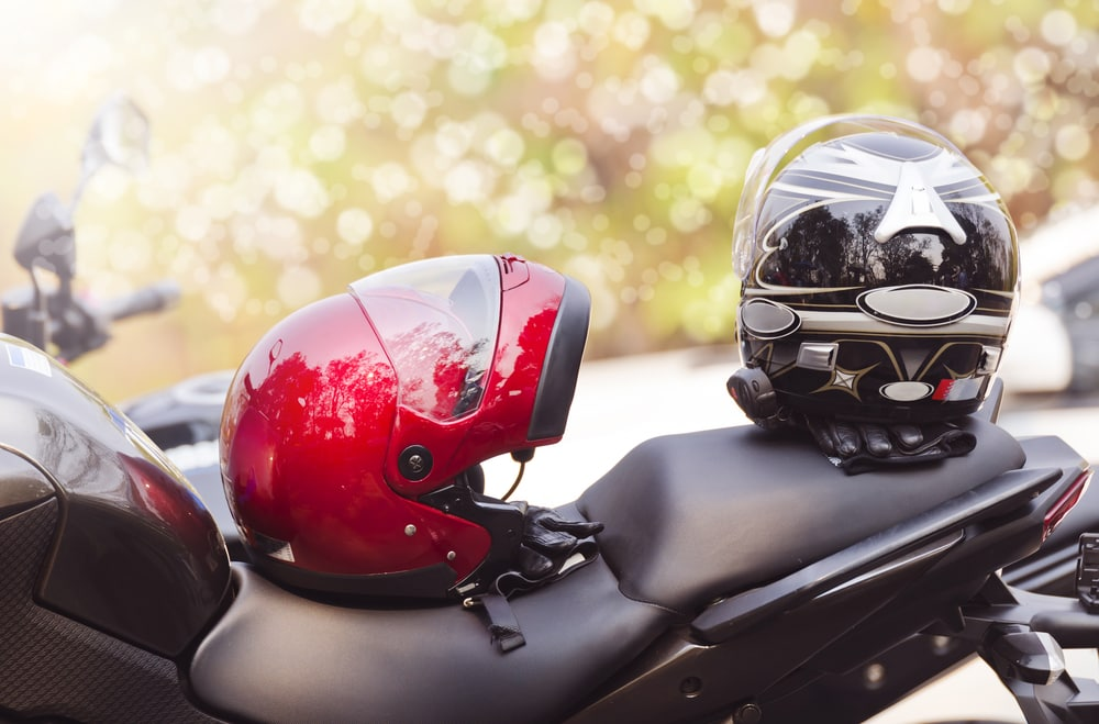 two helmets on top of a motorcycle seat