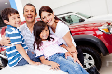 happy family at dealership buying a used car