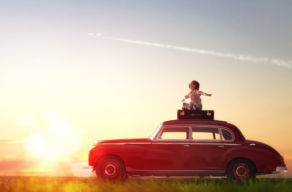 chlid on top of a classic parked car with a suit case