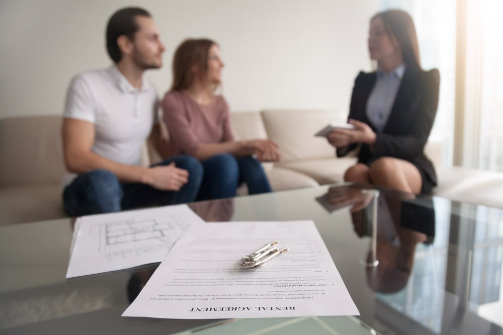 young couple renting for the first time looking over contract with landlord