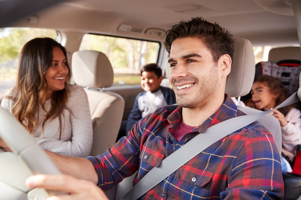 happy hispanic family in a car traveling with kids