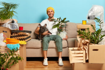 young man in hist first rental apartment with boxes and dog
