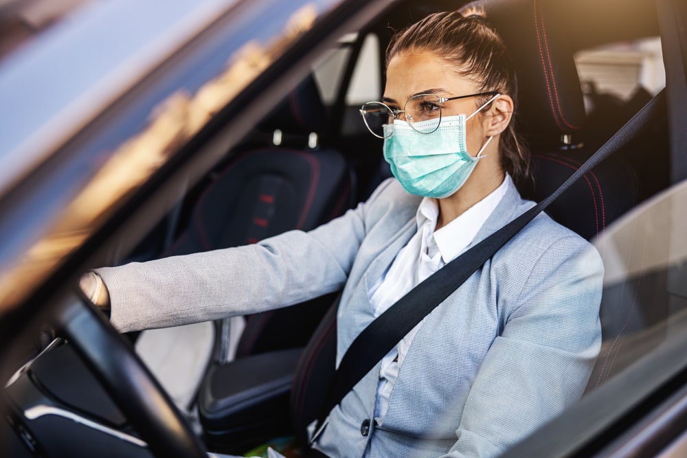young woman in car with mask wondering about car insurance costs