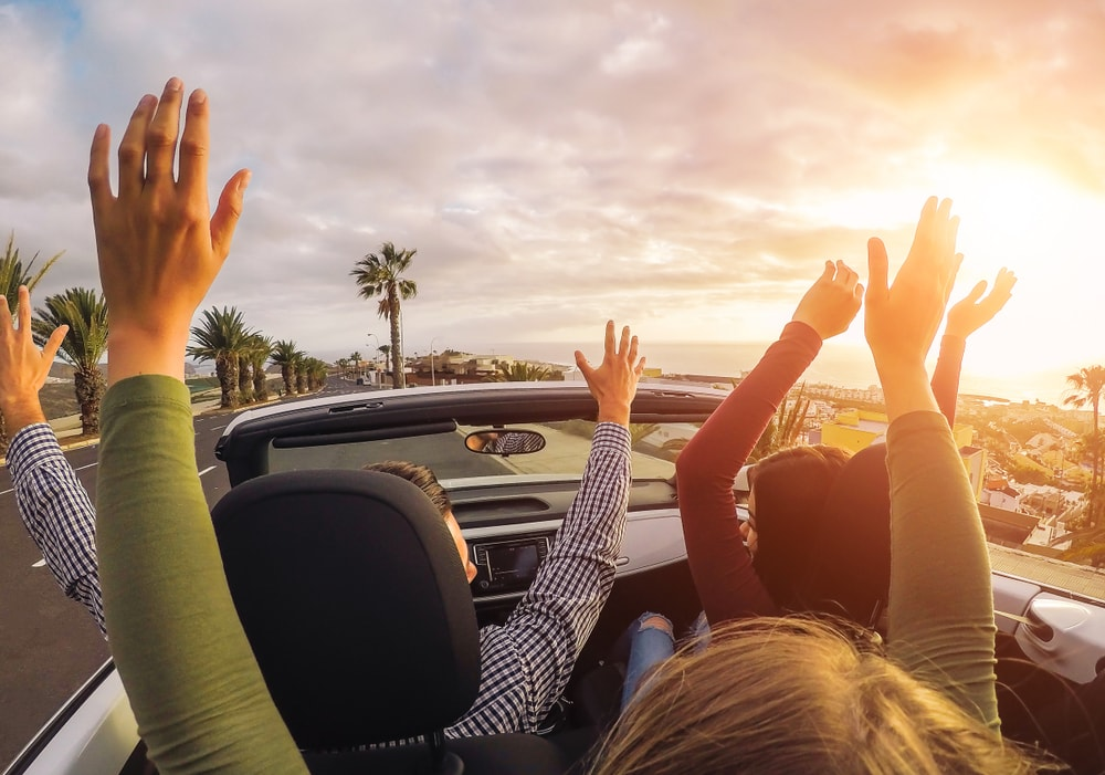 four young people raising hand in convertible car