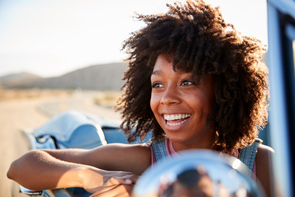happy young woman on convertible car in a california road with cheap car insurance