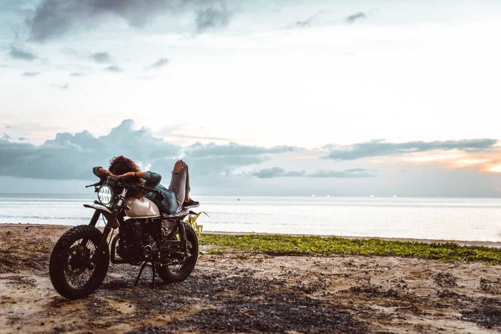 woman in motorcycle parked in front of a california beach with insurance