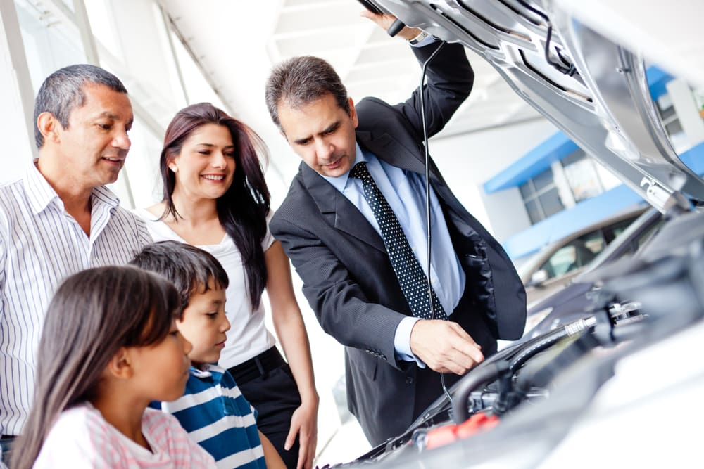 family looking at used car engine to buy it with salesman