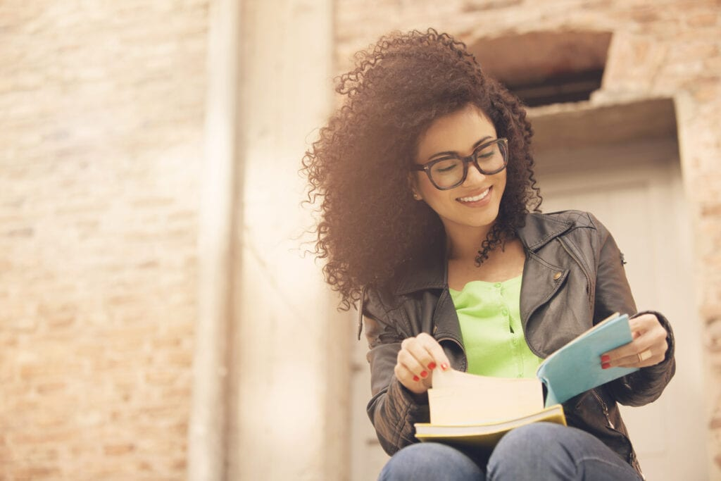 African american young woman smiling with books
