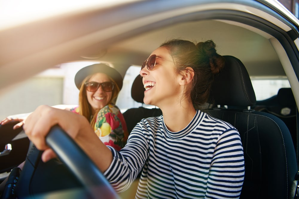 two happy young women in car driving around in california with insurance