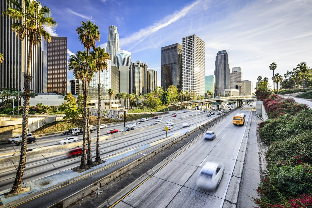 panoramic view of california highway with skyline and insured cars