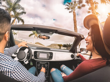 happy hispanic couple on car with cheap auto insurance