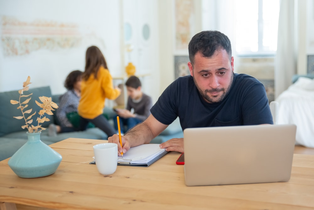 man looking at laptop and taking notes with family on the background