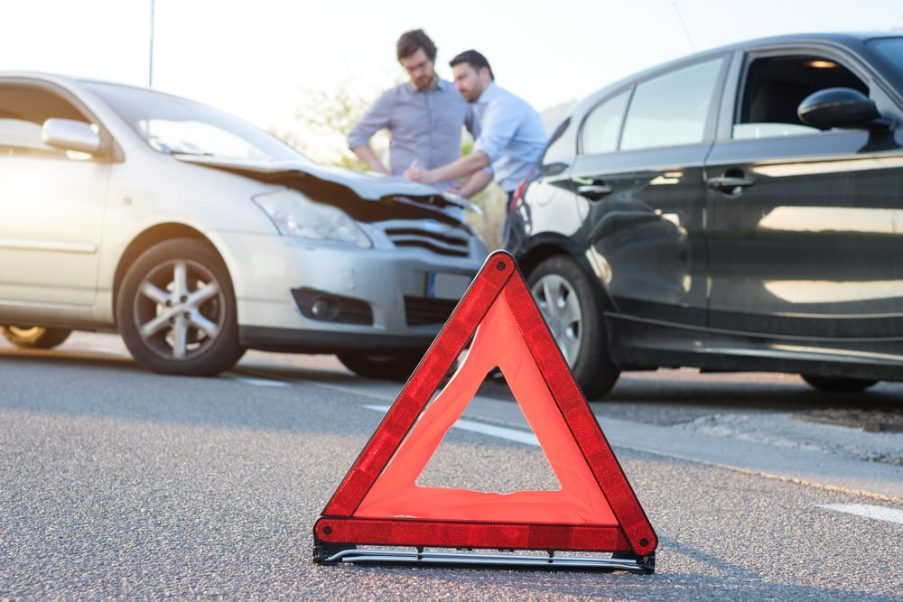 emergency sign with a car accident with two men with collision insurance in california in the back