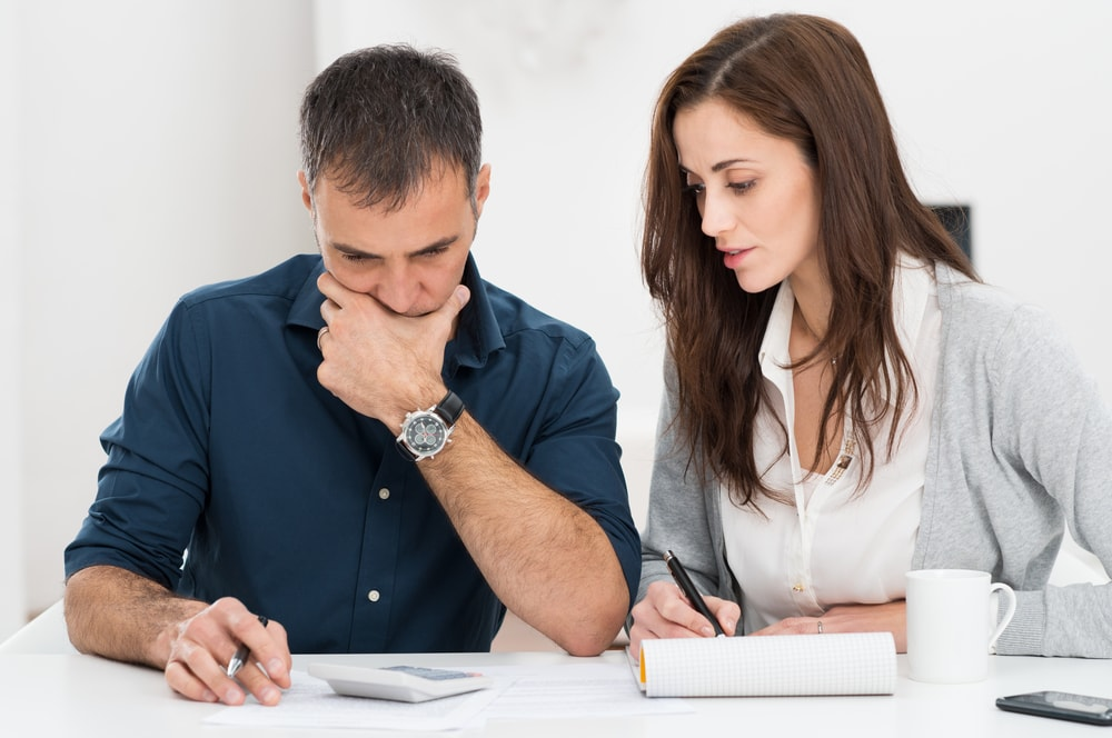 couple looking at car insurance policy to increase deductible
