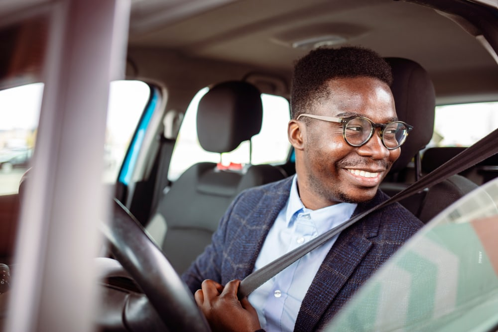 smiling african american man putting on seatbelt in drivers seat