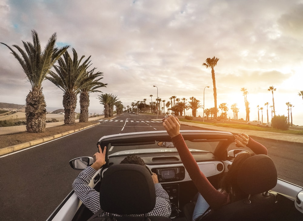 Happy people having fun in convertible car in summer vacation